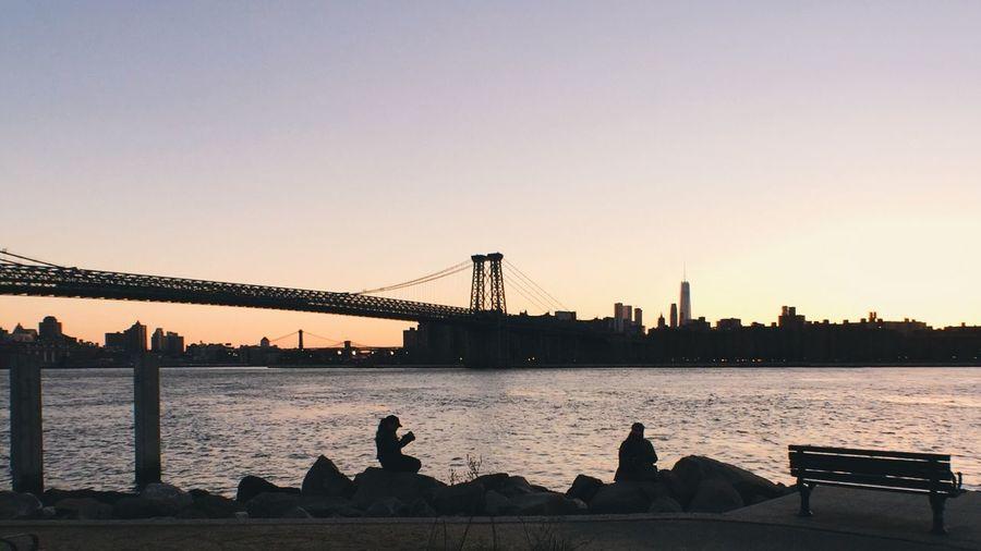 Suspension bridge over river at sunset