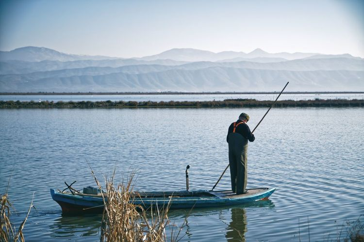 Rear view of man fishing in lake against mountains