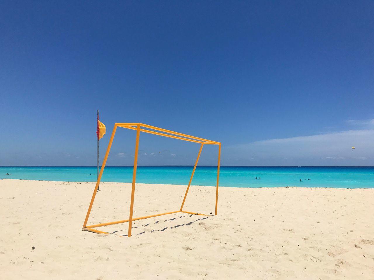 Soccer Goal Post At Sandy Beach Against Blue Sky