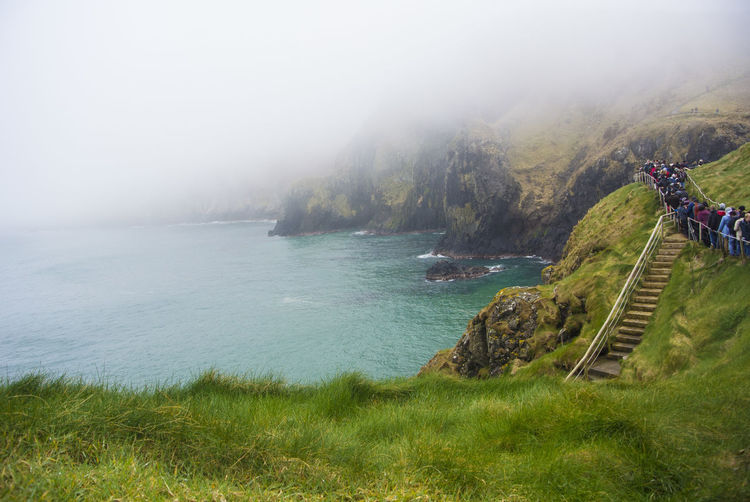Carrick-a-rede Beauty In Nature Day Fog Grass Group Of People Land Men Mountain Nature Outdoors People Plant Real People Scenics - Nature Sea Tranquil Scene Tranquility Water EyeEmNewHere My Best Travel Photo