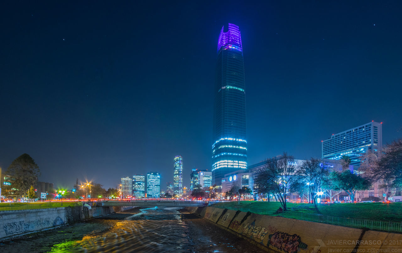 architecture, skyscraper, building exterior, modern, tall - high, built structure, city, tower, night, illuminated, development, travel destinations, water, outdoors, sky, urban skyline, cityscape, tall, clear sky, no people, nature
