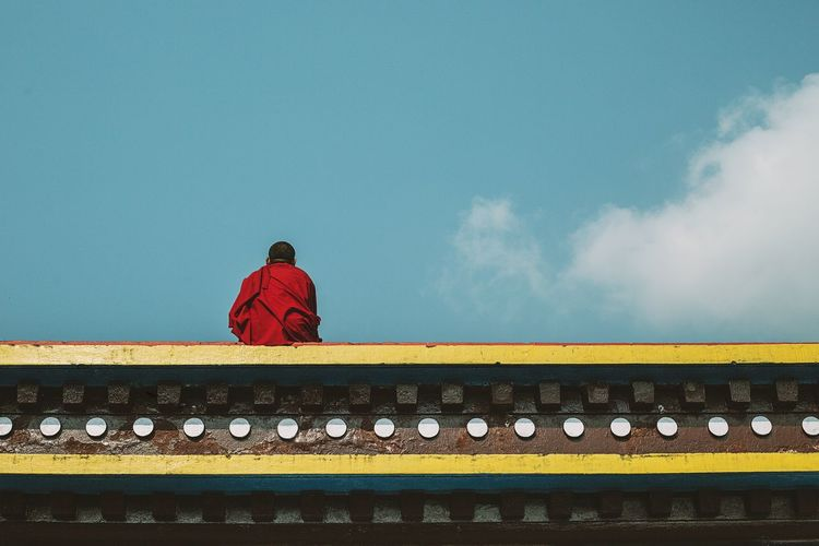 Rear view of a monk against blue sky