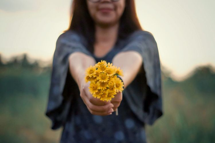 Midsection of man holding yellow flower