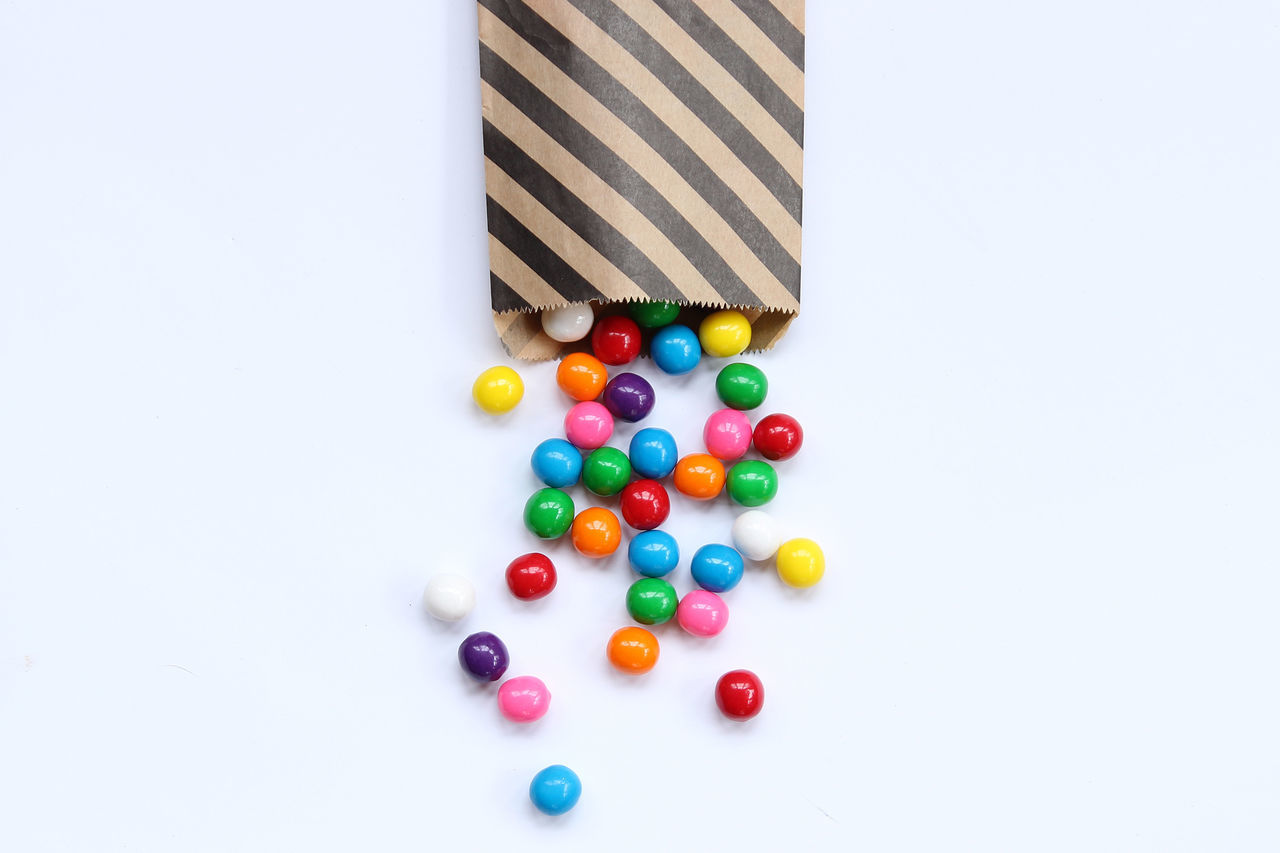 Directly Above Shot Of Colorful Gumballs From Paper Bag On White Background