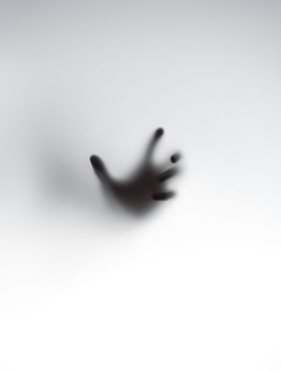 Shadow of hand on glass against white background