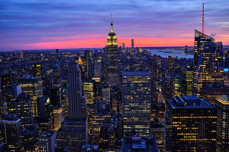 Illuminated cityscape against romantic sky at sunset