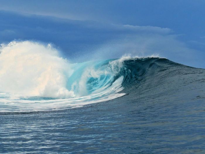 Scenic view of waves against blue sky