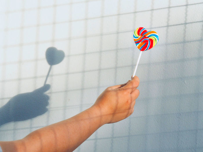 Close-up of hand holding rainbow colorful lollipop against table wall lgbt