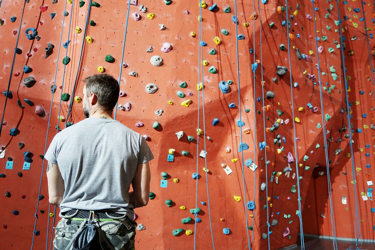 Rear view of man standing against climbing wall