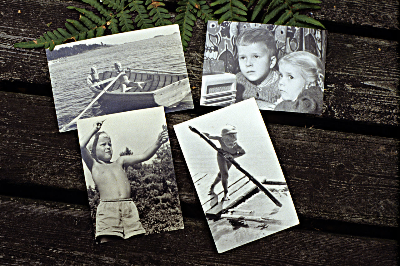 High Angle View Of Boy And Girl Photographs On Wooden Table