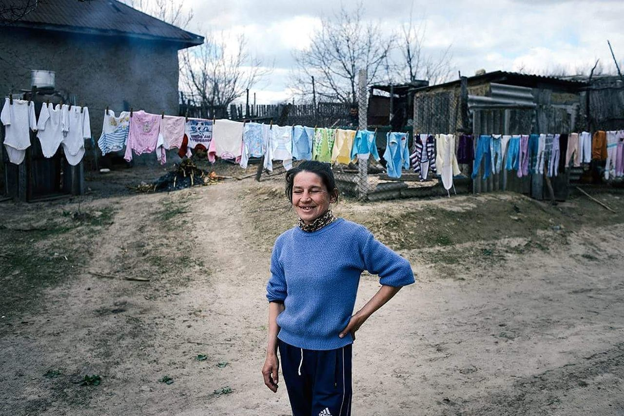 PORTRAIT OF SMILING YOUNG WOMAN HANGING ON CLOTHESLINE