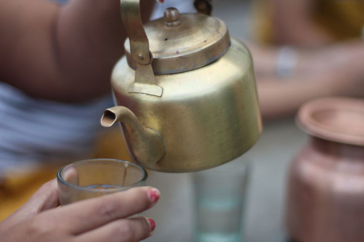 Close-up of hand pouring tea in cup from kettle