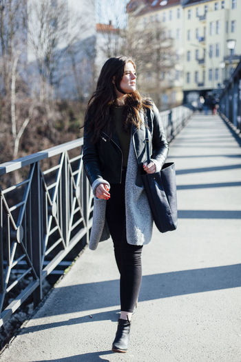 Beautiful young woman walking on footbridge during sunny day