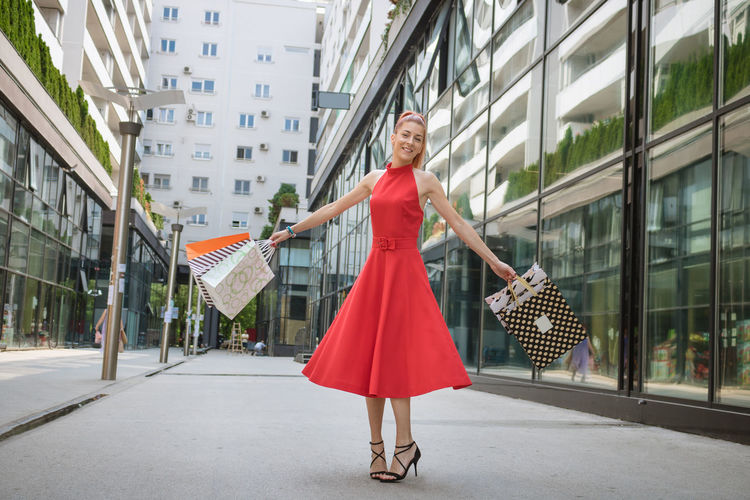 Woman holding umbrella in city