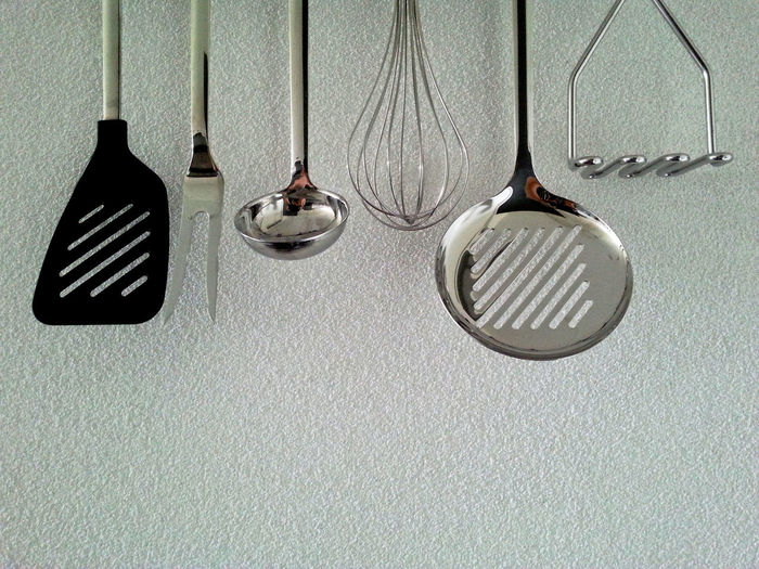 Close-up of kitchen utensils hanging from wall