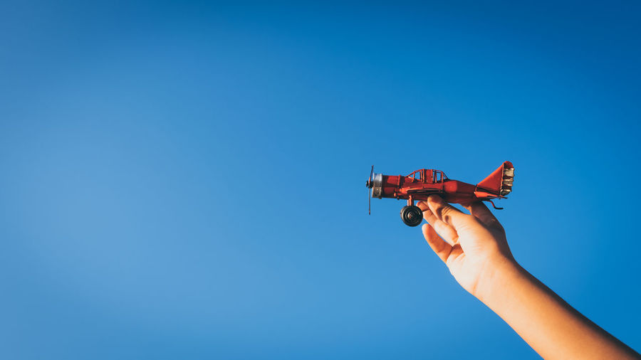 Low angle view of hand holding toy airplane against clear blue sky