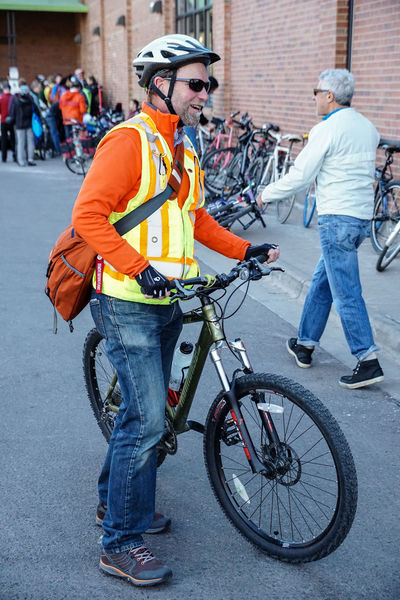 Cyclist commuter with his bike gear. Other cyclists gather in the background. Bicycle Bike Rider Biking City Colorful Commuter Commuting Cycling CyclingUnites Cyclist Day Headwear Helmet Man Mountain Bike Outdoors Travel Urban