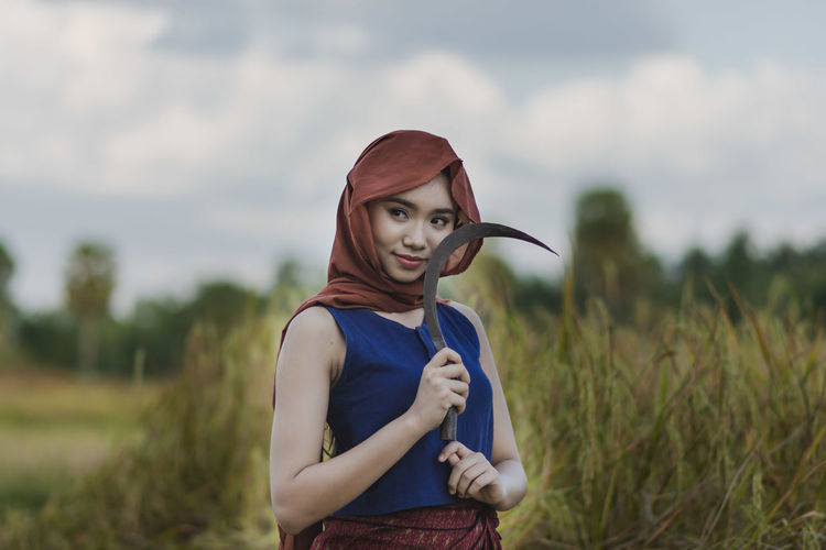 Thoughtful Teenage Girl Holding Knife While Standing On Field