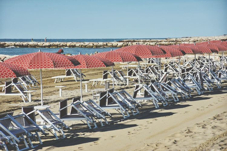 Chairs on beach against clear sky