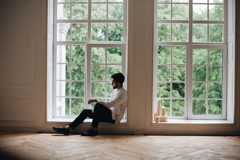 Man Sitting On Window Sill At Home