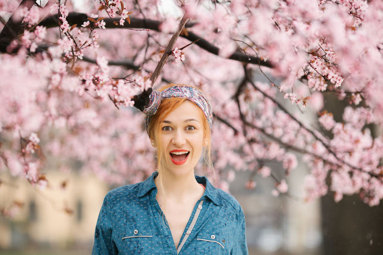 Portrait of happy young woman with pink cherry blossoms against trees