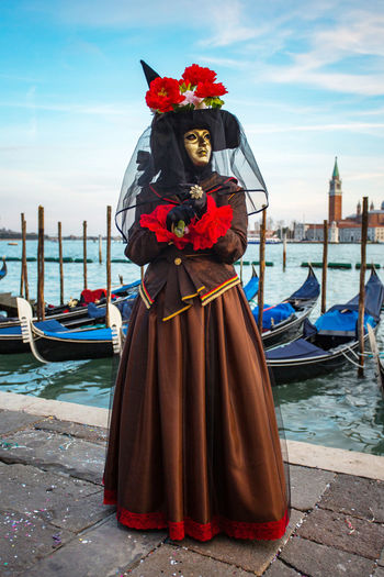 Woman wearing costume and mask against gondolas during venice carnival