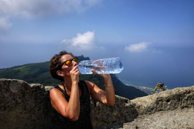 Woman drinking water from bottle against rock and sky