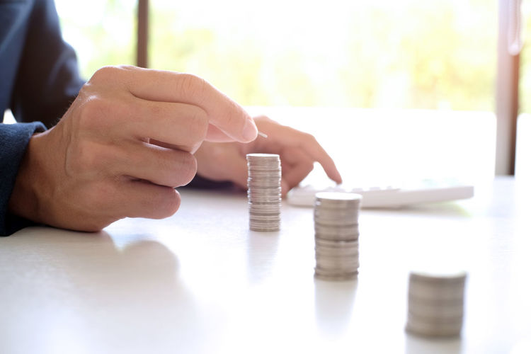 Cropped hands calculating coins on table