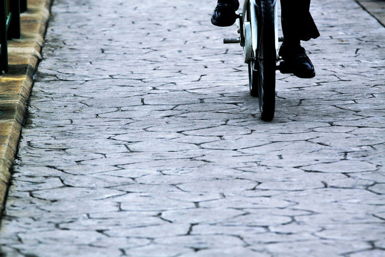 Low section of person riding bicycle on cobbled street