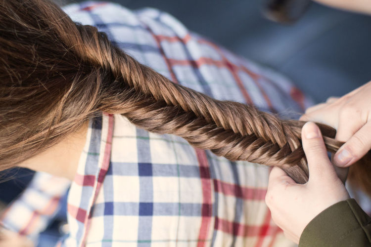 Close-Up Of Hands Braiding Hairs Of Friend
