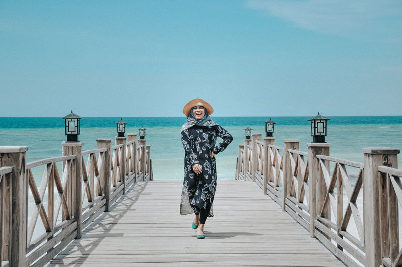 Young woman walking on footpath against sea