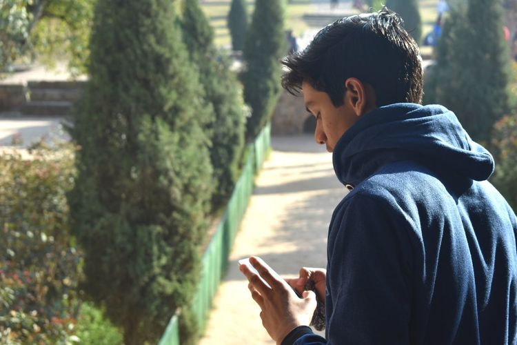 Side view of young man using mobile phone on footpath