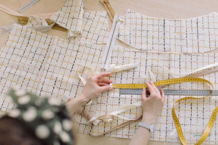 High angle view of woman measuring fabric with tape and ruler on table