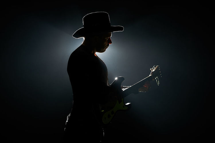 Side view of silhouette mid adult man playing guitar against black background