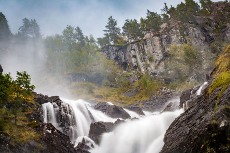 Beauty In Nature Blurred Motion Cliff Day Long Exposure Low Angle View Motion Mountain Nature No People Outdoors Power In Nature River Rock - Object Scenics Tourism Tree Water Waterfall