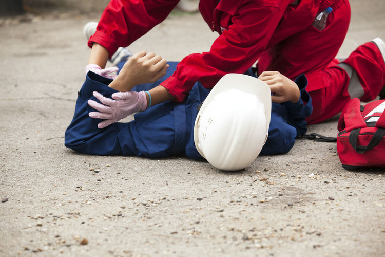 Paramedic performing cpr on person lying on street