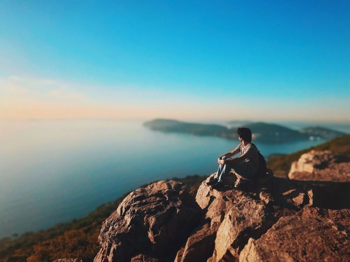 Man sitting on cliff against sea during sunset