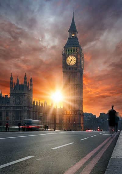 Blurred motion of vehicles on road by big ben against sky during sunset
