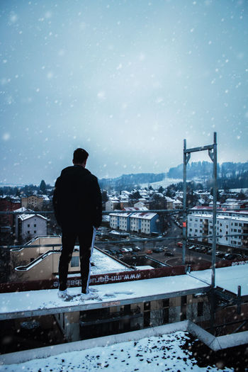 Rear view of man standing on snow covered cityscape