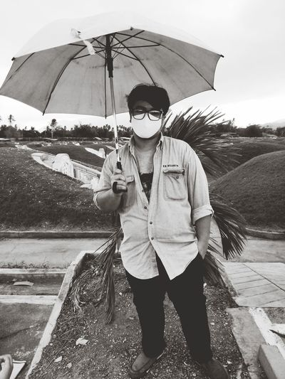 Full length of young man standing on umbrella during rainy season