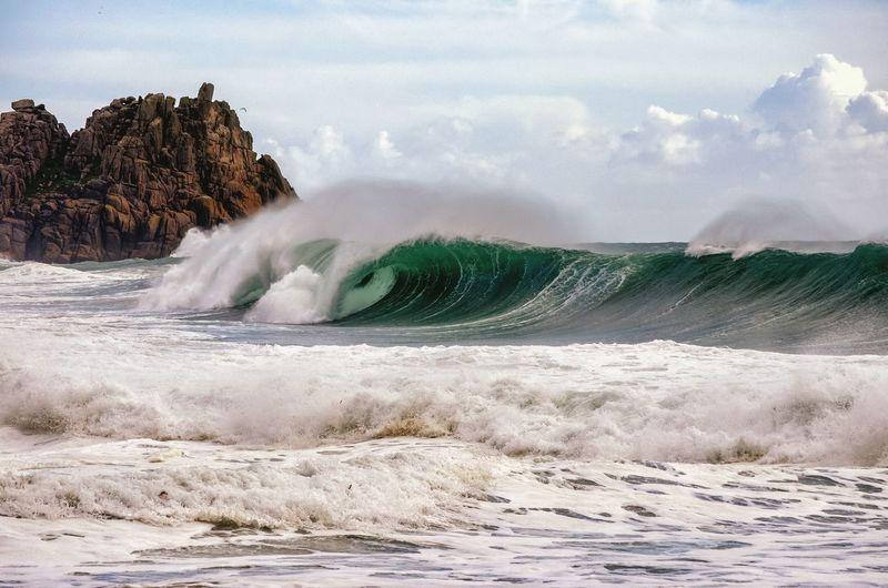 Waves rushing towards sea shore against sky