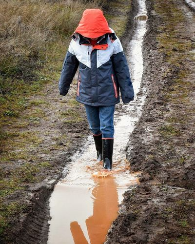 Full Length Of Boy Walking On Muddy Pathway Amidst Field