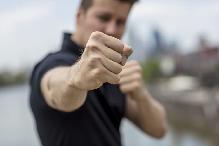 A man ready to fight with his guard up. A city skyline with high rise buildings is visible in the background in blur. Medium close up. Focus on fist. Adult Boxing City Cityscape Fight Frankfurt Am Main Looking At Camera Man Shallow Depth Of Field Caucasian Ethnicity Close Up Fighting Stance Fist Germany Golf Shirt Hairstyle Knuckles Main River Metropolis Pugilism River Short Sleeved Stance Tough Urban