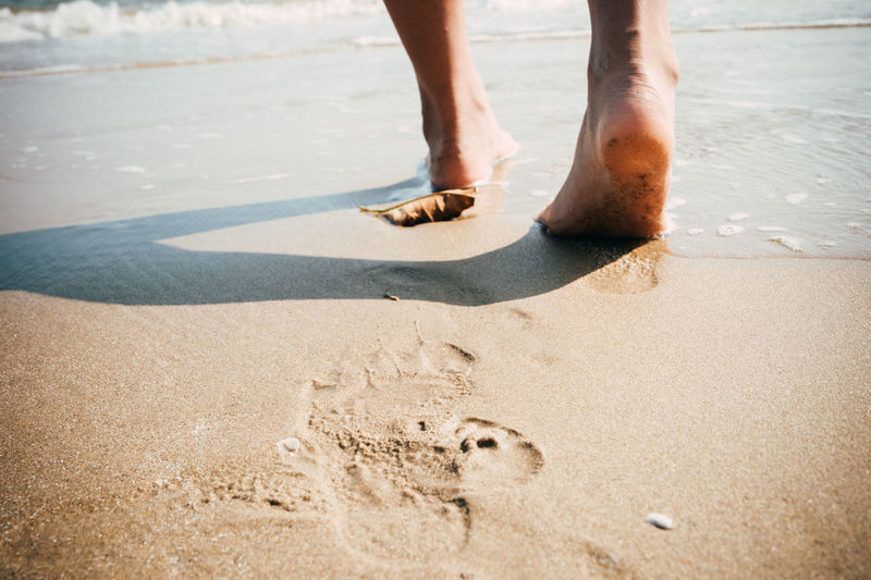 Beach travel - woman walking on sand beach Adult Adults Only Beach Close-up Day Human Body Part Human Leg Leisure Activity Low Section Nature One Man Only One Person Only Men Outdoors People Sand Sea Standing Summer Vacations