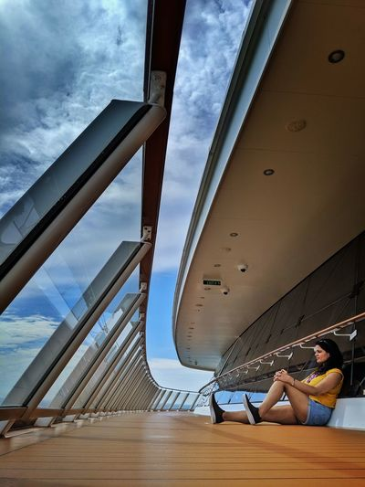 Rear view of woman sitting on railing against sky