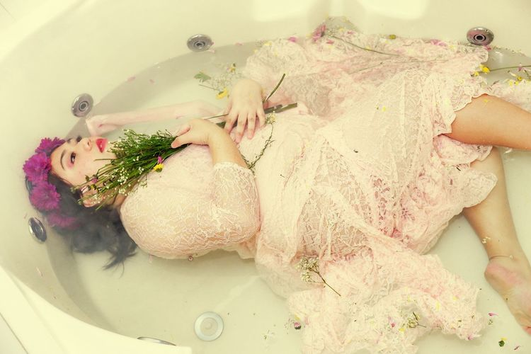 High angle view of woman wearing wedding dress lying in bathtub