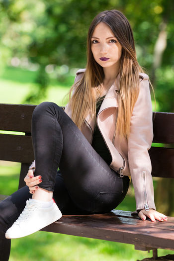 Portrait of beautiful woman relaxing on bench at park
