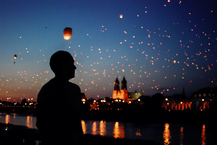 Man looking at sky lanterns flying over river during dusk