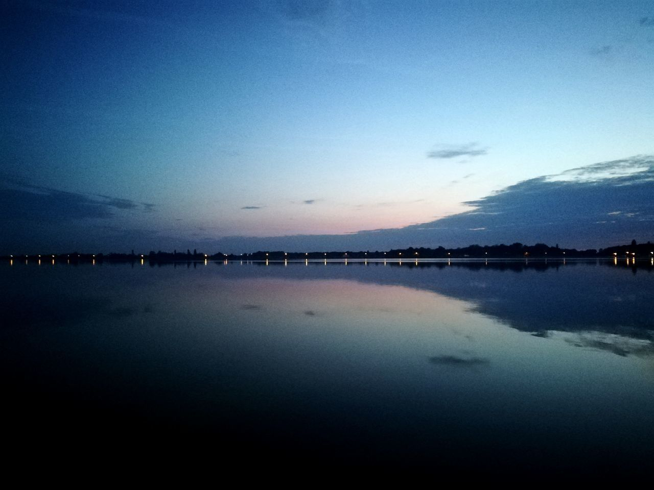 sky, water, tranquil scene, reflection, scenics, tranquility, blue, beauty in nature, dusk, nature, sunset, silhouette, outdoors, no people, lake, cloud - sky, day