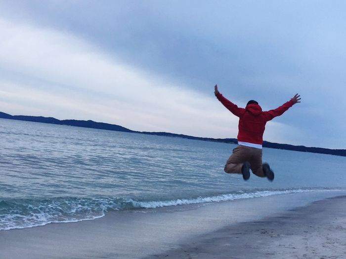 Rear view of excited man jumping on shore at beach against cloudy sky
